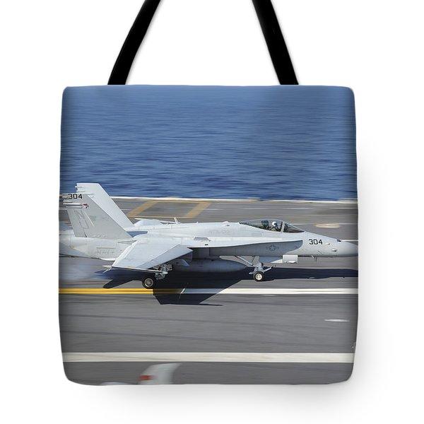 An Fa-18c Hornet Lands Aboard Uss Tote Bag by Stocktrek Images