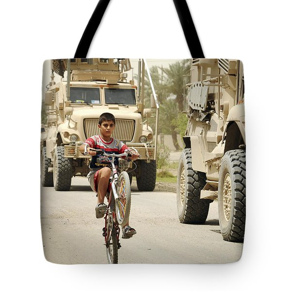 An Iraqi Boy Rides His Bike Past A U.s Tote Bag by Stocktrek Images