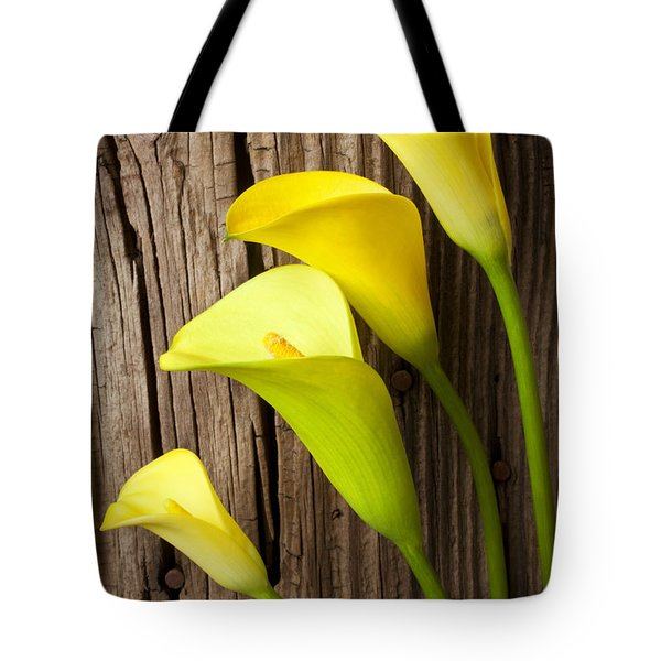 Calla lilies against wooden wall Tote Bag by Garry Gay