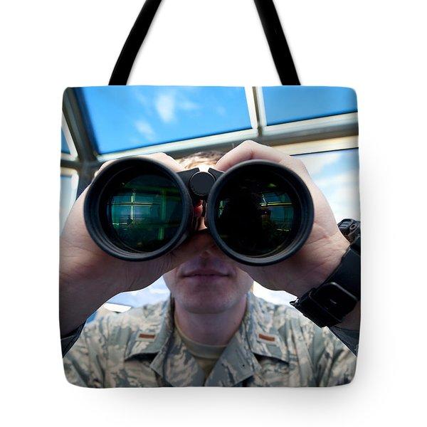 Lieutenant Uses Binoculars To Scan Tote Bag by Stocktrek Images