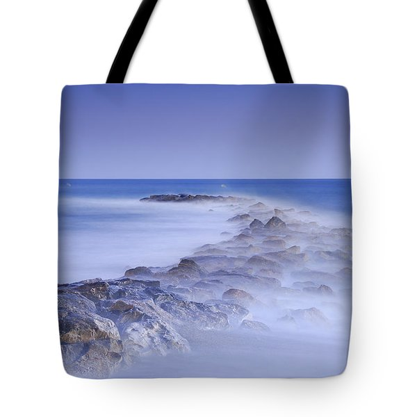 Rocks fighting against the waves Tote Bag by Guido Montanes Castillo