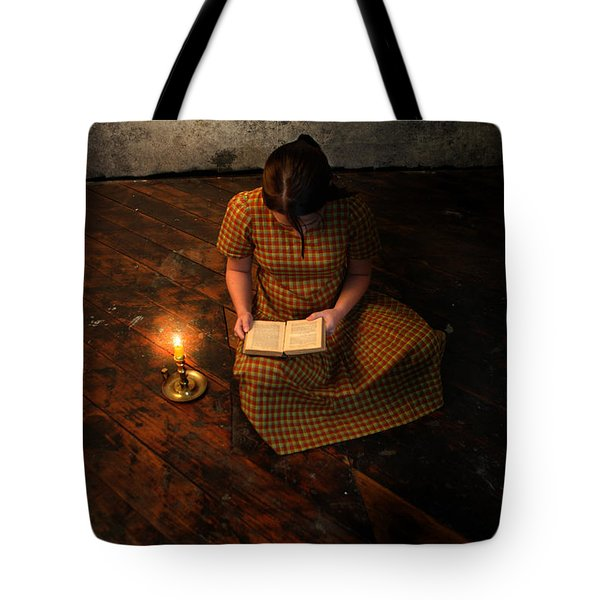 Schoolgirl Sitting On Wood Floor Reading By Candlelight Tote Bag by Jill Battaglia