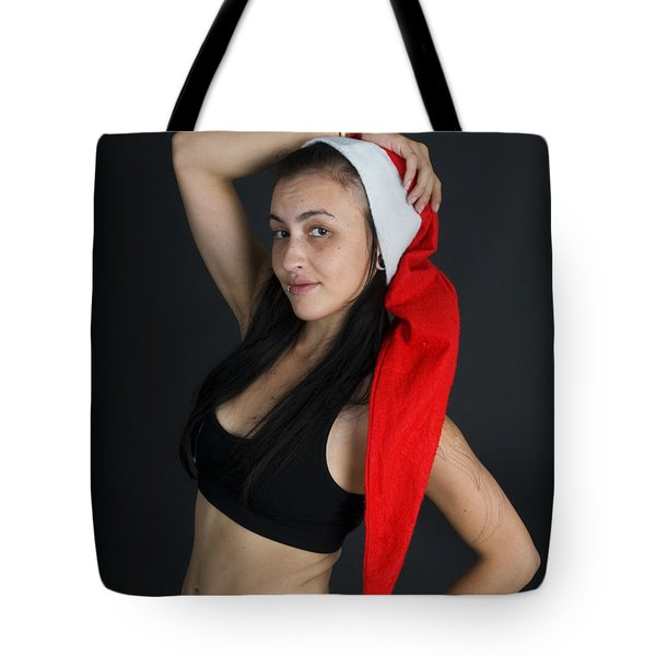 Young woman wearing Santa hat Tote Bag by Ilan Rosen
