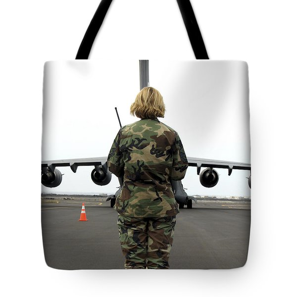 An Airfield Manager Greets An Arriving Tote Bag by Stocktrek Images