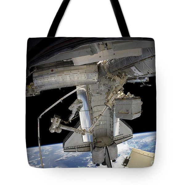 Astronaut Participates In A Spacewalk Tote Bag by Stocktrek Images