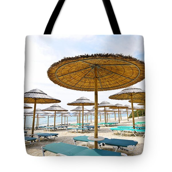 Beach umbrellas and chairs on sandy seashore Tote Bag by Elena Elisseeva