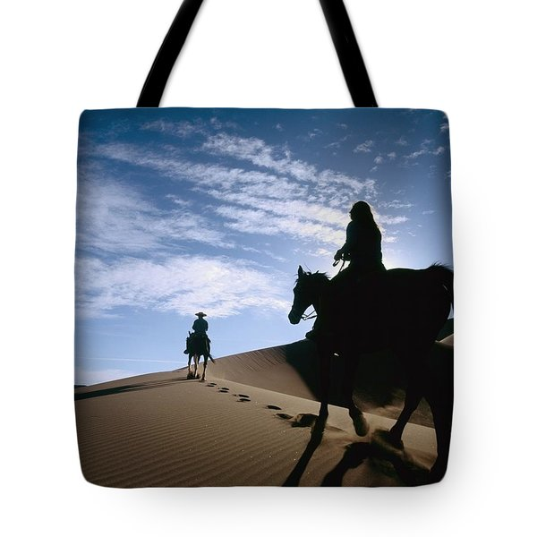 Horseback Riders In Silhouette On Sand Tote Bag by Axiom Photographic