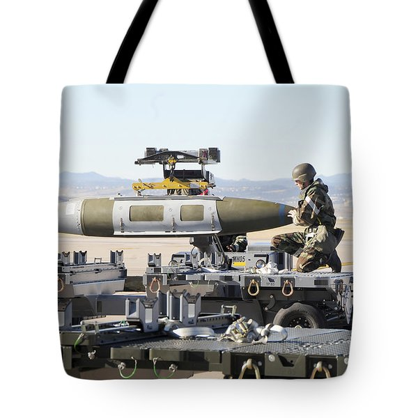 Irman Assists In Lowering A Guided Bomb Tote Bag by Stocktrek Images