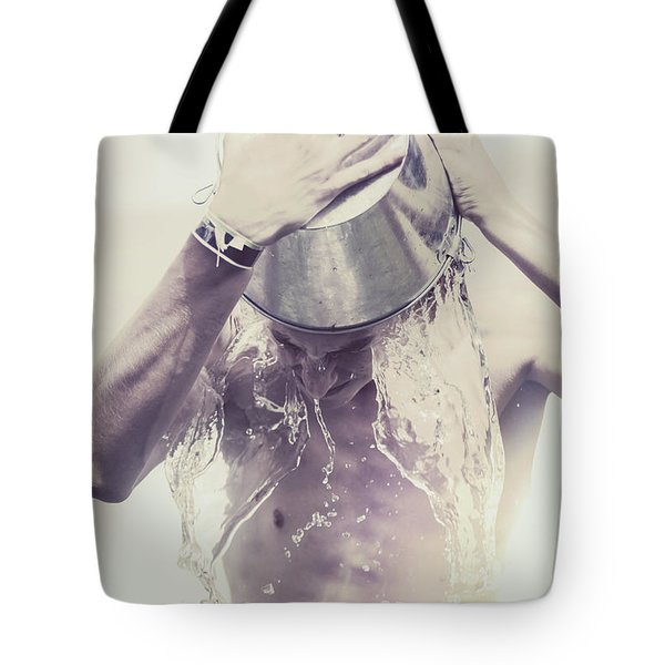 Man pouring cold water from wine cooler over body Tote Bag by Ryan Jorgensen