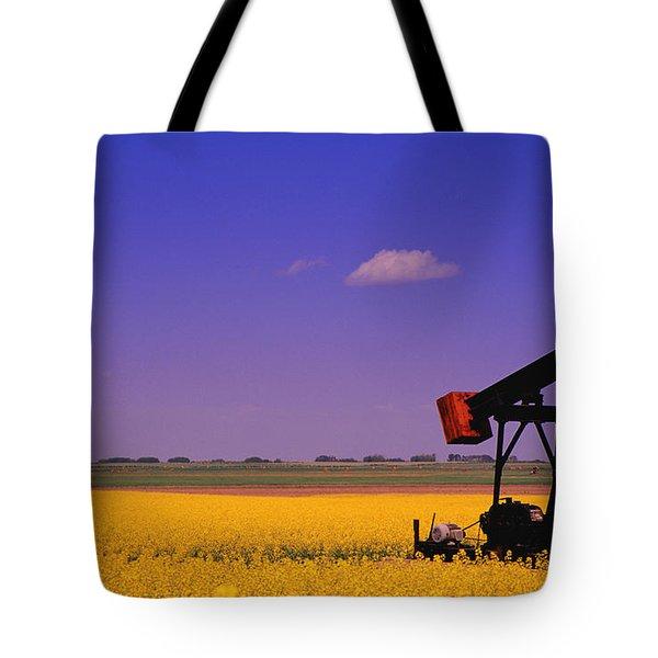Pumpjack In A Canola Field Tote Bag by Carson Ganci