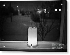 candle in the window looking out over snow covered scene in small rural village of Forget Saskatchew Acrylic Print by Joe Fox