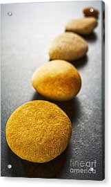 Diagonal Line Of Brown Pebbles On Dark Background Acrylic Print by Colin and Linda McKie