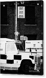Armoured Psni Land Rovers Under Protest Sign Banner On Crumlin Road At Ardoyne  Acrylic Print by Joe Fox