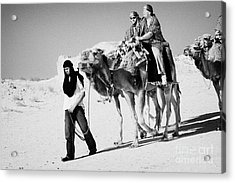 bedouin guide in modern clothing leads british tourists riding camels and wearing desert clothes into the sahara desert at Douz Tunisia Acrylic Print by Joe Fox