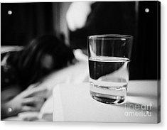 Glass Of Water On Bedside Table Of Early Twenties Woman In Bed In A Bedroom Acrylic Print by Joe Fox