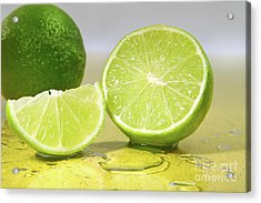 Limes On Yellow Surface Acrylic Print by Sandra Cunningham