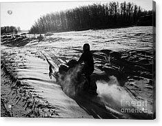 man on snowmobile crossing frozen fields in rural Forget canada Acrylic Print by Joe Fox