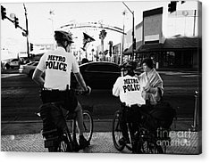metro police bicycle cops help a tourist with directions in downtown Las Vegas Nevada USA Acrylic Print by Joe Fox