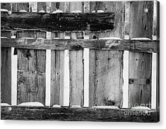 old patched up wooden fence using old bits of wood in snow Forget Acrylic Print by Joe Fox