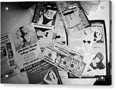 selection of leaflets advertising girls laid out on a hotel bed with us dollars cash in Las Vegas Ne Acrylic Print by Joe Fox