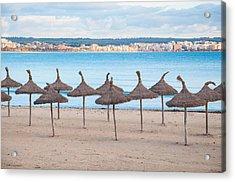 Straw Umbrellas On Empty Beach Acrylic Print by Christina Rahm