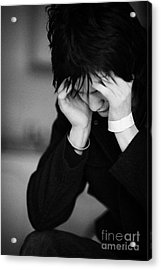 Young Dark Haired Teenage Man Sitting With His Head In His Hands Staring At The Floor Acrylic Print by Joe Fox