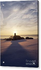 Snow Covered Field With Farm Silhouette At Sunset Acrylic Print by Jeremy Woodhouse