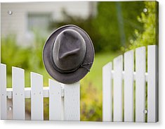 A Hat Hanging On The Post Of A White Acrylic Print by Lorna Rande