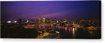 Aerial View Of A City Lit Up At Dusk Canvas Print by Panoramic Images