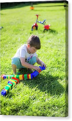 Boy Playing With Plastic Bricks Canvas Print by Samuel Ashfield