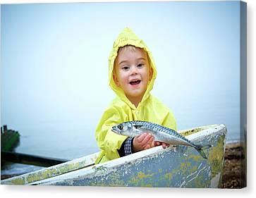 Boy Wearing Raincoat Holding A Mackerel Canvas Print by Ruth Jenkinson
