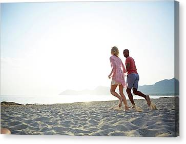 Couple Running On The Beach Canvas Print by Ruth Jenkinson