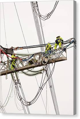 Engineers Working On Electricity Wires Canvas Print by Ashley Cooper