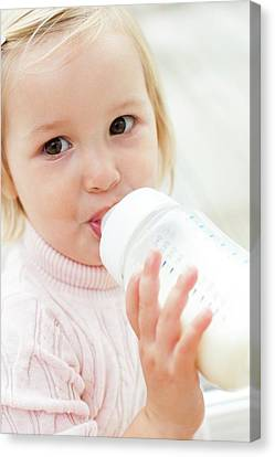 Toddler Holding A Bottle Of Milk Canvas Print by Ian Hooton