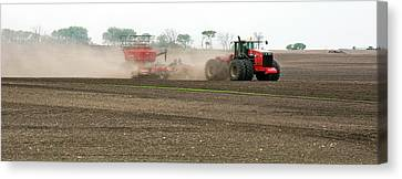 Tractor Ploughing A Field Canvas Print by Jim West