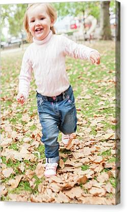 Young Girl Running In The Leaves Canvas Print by Ian Hooton