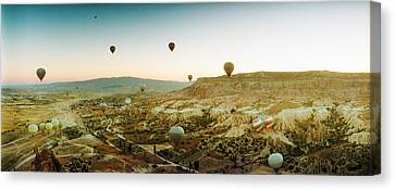 Hot Air Balloons Over Landscape Canvas Print by Panoramic Images