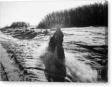 man on snowmobile crossing frozen fields in rural Forget Saskatchewan Canada Canvas Print by Joe Fox