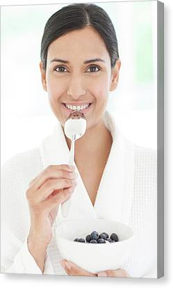 Woman Holding Bowl Of Fruit And Spoon Canvas Print by Ian Hooton