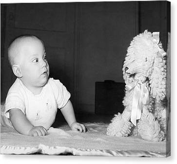 A Baby And A Toy Dog Canvas Print by Orville Andrews