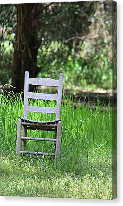 A Chair In The Grass Canvas Print by Lynn Jordan