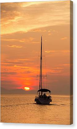 A Sailing Boat At Sunset Canvas Print by Ashley Cooper