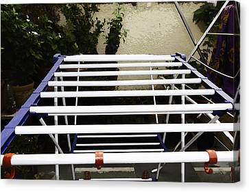 A White Plastic Stand For Hanging And Drying Clothes Canvas Print by Ashish Agarwal