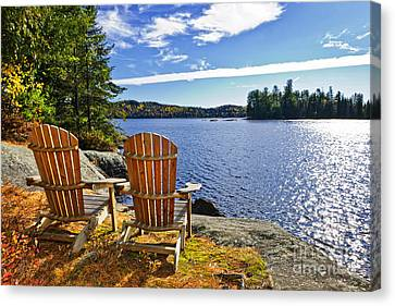 Adirondack Chairs At Lake Shore Canvas Print by Elena Elisseeva