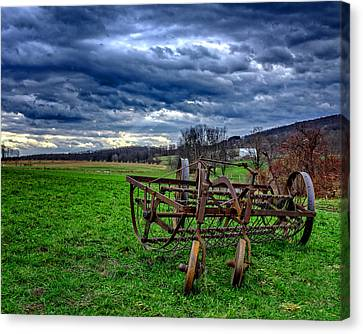 Antique Hay Rake Under As Stormy Sky Canvas Print by Chris Bordeleau