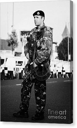 Armed British Soldier On Crumlin Road At Ardoyne Shops Belfast 12th July Canvas Print by Joe Fox