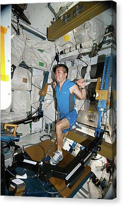Astronaut Exercising On The Iss Canvas Print by Nasa