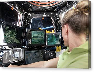 Astronaut In Iss Robotics Workstation Canvas Print by Nasa