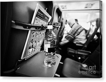 Bottle Of Water On Tray Table Interior Of Jet2 Aircraft Passenger Cabin In Flight Europe Canvas Print by Joe Fox