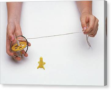Boy's Hands Holding Gyroscope With String Canvas Print by Dorling Kindersley/uig